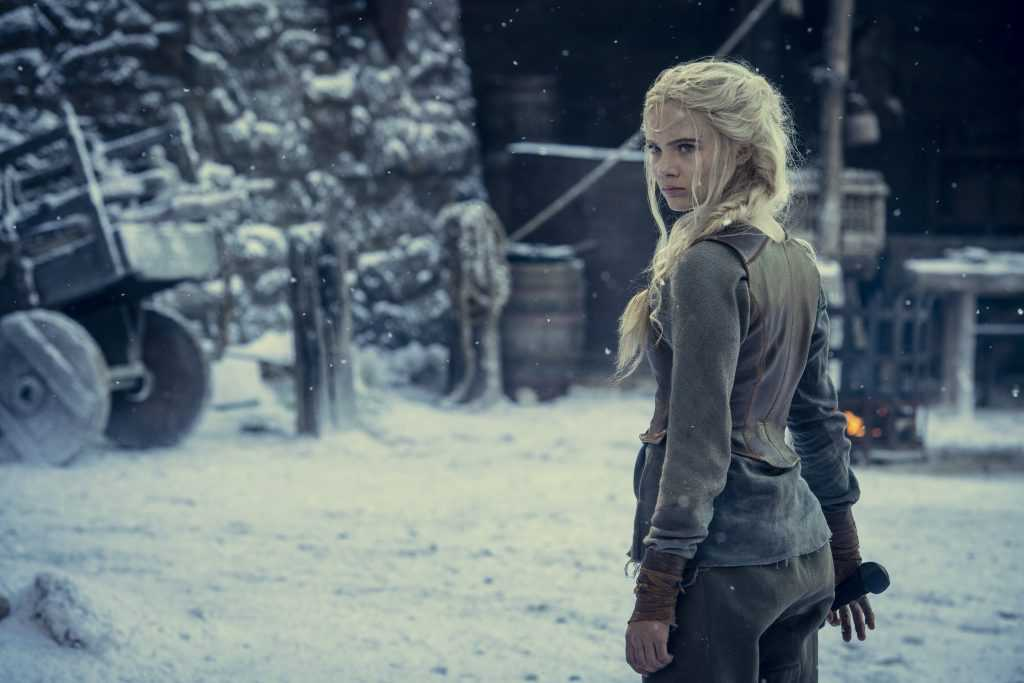 Freya Allan as Princess Ciri from The Witcher. Standing in a snowy set, the character has her back to the camera and is grabbing a sword. It looks like she's training