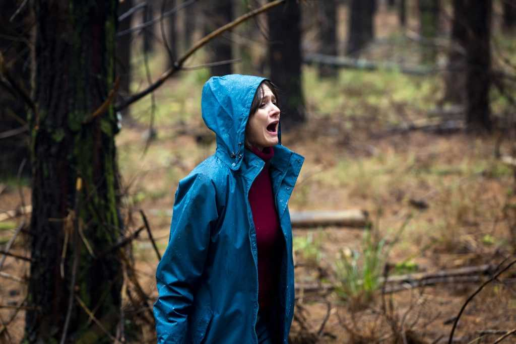 Actress Emily Mortimer screaming in a woodland wearing a blue anorak, from the film Relic.