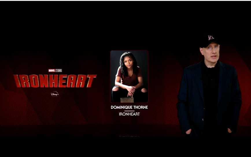 Marvel President Kevin Feige standing in front of the Ironheart logo next to a photo of actor Dominique Thorne
