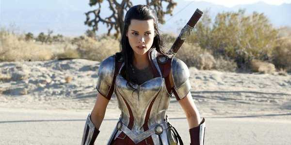 Jamie Alexander suited up in full army with a sword on her back as Lady Sif. There's a sandy, desert looking background.
