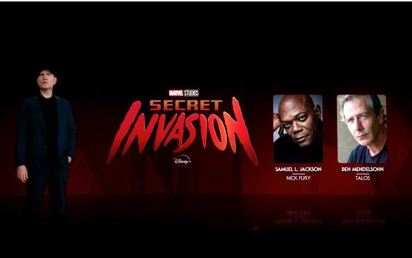 Marvel President Kevin Feige standing in front of the Secret Invasion logo and photos of Samuel L Jackson and Ben Mendelsohn