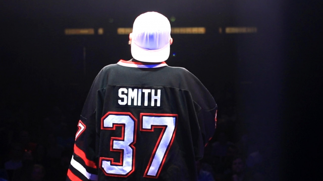Kevin Smith talking in front of a crowd with his ice hockey jersey on, (Smith and has a number 37) along with a white baseball cap